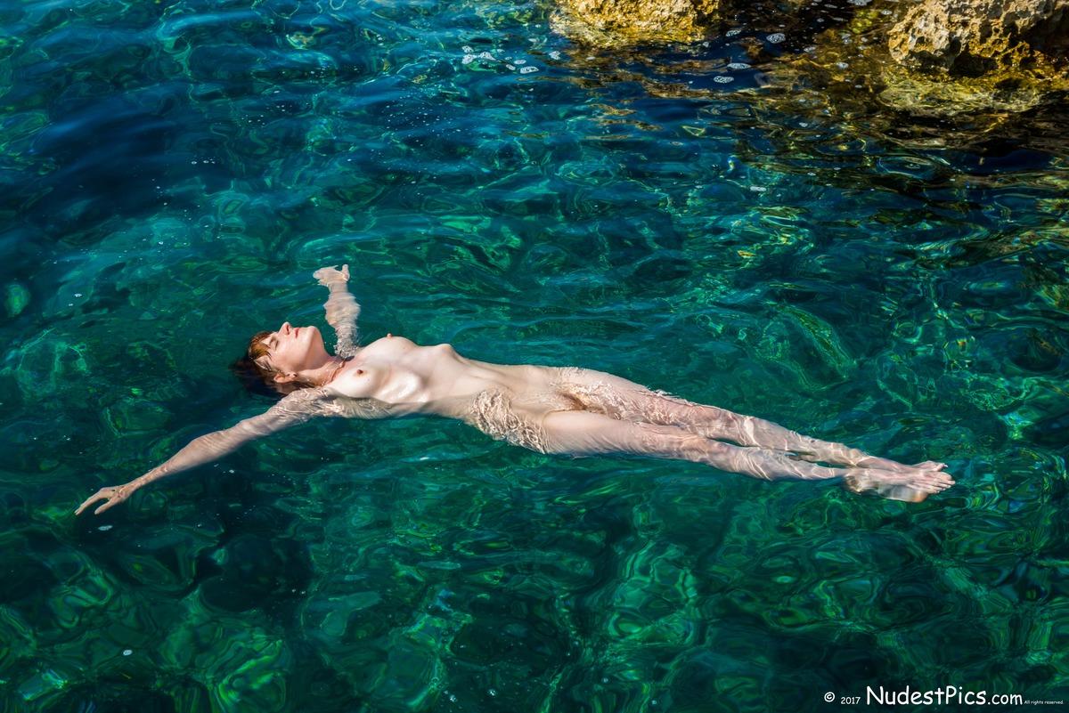 Nudist Girl Floating on Turquoise Sea Water